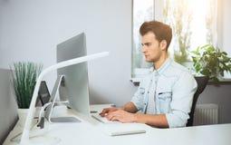 Trabalhador novo que senta-se em um escritório no computador Freelancer em uma camisa branca O desenhista senta-se na frente da j Fotografia de Stock Royalty Free