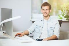 Trabalhador novo que senta-se em um escritório no computador Freelancer em uma camisa branca O desenhista senta-se na frente da j Fotografia de Stock