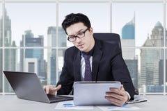 Trabalhador novo que usa a tabuleta e o portátil Foto de Stock