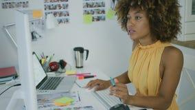 Trabalhador pensativo à moda no desktop video estoque