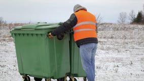 Trabalhador perto dos recipientes do lixo no inverno video estoque