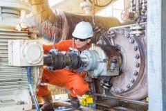Trabalhador a pouca distância do mar da plataforma petrolífera, técnico mecânico que inspeciona a bomba centrífuga do óleo foto de stock