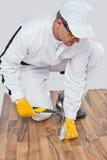 Trabalhador pregado com um assoalho de madeira do martelo Imagens de Stock Royalty Free