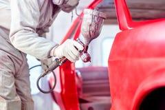 Trabalhador profissional que pulveriza a pintura vermelha em um corpo de carro Fotografia de Stock Royalty Free