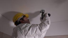 Trabalhador qualificado com furos de perfuração do capacete no teto video estoque