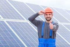 Trabalhador que aferra-se ao capacete de segurança e que mostra o polegar acima contra o fundo dos painéis solares fotos de stock