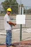Trabalhador que afixa o sinal em branco Imagens de Stock Royalty Free