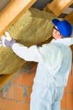 Trabalhador que ajusta o material de isolamento térmico Fotografia de Stock