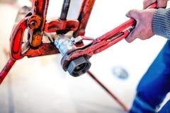 Trabalhador que aperta as tubulações na instalação do encanamento fotografia de stock royalty free