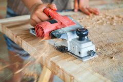 Trabalhador que aplana um tampo da mesa da madeira com um plano bonde fotos de stock royalty free