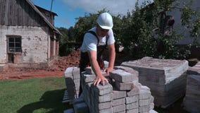 Trabalhador que classifica tijolos filme
