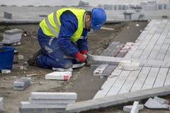 Trabalhador que coloca pedras de pavimentação imagens de stock