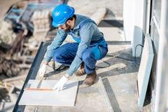 Trabalhador que coloca telhas no balcão imagens de stock