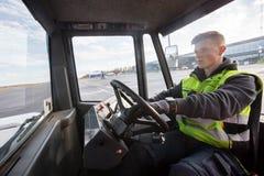 Trabalhador que conduz o caminhão de reboque na pista de decolagem imagem de stock