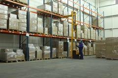 Trabalhador que conta estoques no armazém Fotos de Stock