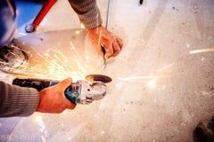 Trabalhador que corta as barras de aço usando o moedor manual industrial fotos de stock royalty free
