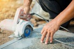 Trabalhador que corta a pedra do granito com uma lâmina de serra do diamante e água elétricas do uso para impedir a poeira e o ca fotografia de stock