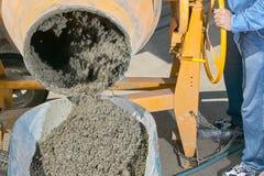 Trabalhador que derrama o cimento molhado no carrinho de mão fotografia de stock royalty free