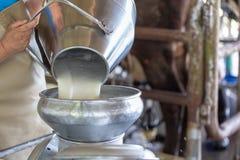 Trabalhador que derrama o leite no recipiente da exploração agrícola foto de stock