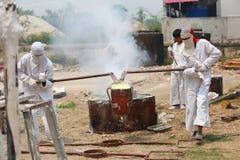 Trabalhador que derrama o metal derretido à estátua de moldação da Buda Fotografia de Stock Royalty Free