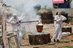 Trabalhador que derrama o metal derretido à estátua de moldação da Buda Fotografia de Stock