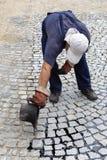 Trabalhador que derrama o passo derretido de uma cubeta do alcatrão Imagem de Stock