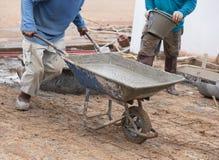 Trabalhador que empurra o carrinho de mão com cimento molhado para o derramamento do assoalho concreto fotografia de stock royalty free