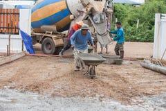 Trabalhador que empurra o carrinho de mão com cimento molhado para o derramamento do assoalho concreto foto de stock royalty free