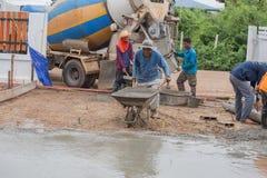 Trabalhador que empurra o carrinho de mão com cimento molhado para o derramamento do assoalho concreto fotos de stock royalty free