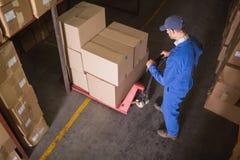 Trabalhador que empurra o trole com as caixas no armazém Fotografia de Stock