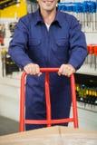 Trabalhador que empurra o trole na loja de ferragens Imagens de Stock