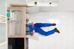 Trabalhador que encontra-se no assoalho que repara o dissipador fotografia de stock