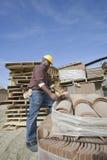 Trabalhador que escolhe uma telha no local Fotografia de Stock Royalty Free