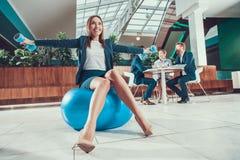 Trabalhador que exercita na bola da aptidão no escritório fotografia de stock