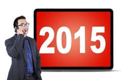 Trabalhador que fala no telefone celular com os números 2015 Foto de Stock Royalty Free