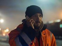 Trabalhador que fala pela luz do bokeh do smartphone no bacground Conceito do turno da noite Fotografia de Stock Royalty Free