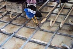 Trabalhador que faz o objeto metálico para o reforço do assoalho concreto no canteiro de obras fotos de stock