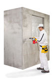 Trabalhador que faz um furo com um perfurador na parede do cimento Foto de Stock