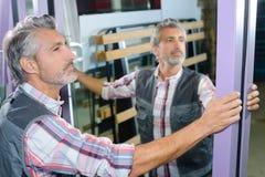 Trabalhador que guarda o espelho de vidro fotografia de stock