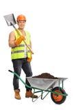 Trabalhador que guarda uma pá ao lado de um carrinho de mão Fotografia de Stock