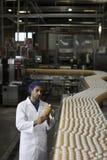 Trabalhador que inspeciona a garrafa do suco de laranja na planta de engarrafamento Imagem de Stock