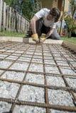 Trabalhador que instala as hastes de ferro para o passeio concreto Fotos de Stock