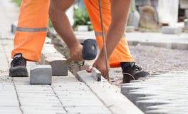 Trabalhador que instala blocos da borda da estrada Foto de Stock Royalty Free
