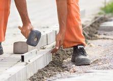 Trabalhador que instala blocos da borda da estrada Imagens de Stock Royalty Free