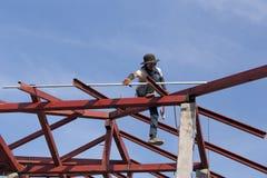 Trabalhador que instala a estrutura do aço do telhado para a casa nova no const Imagens de Stock