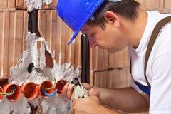 Trabalhador que instala fios elétricos Fotografia de Stock Royalty Free