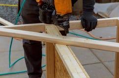 Trabalhador que instala o assoalho de madeira para martelar em um pátio da plataforma fotos de stock