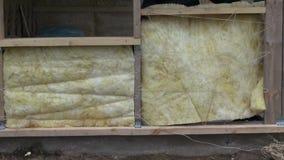 Trabalhador que isola o quadro de madeira da casa com rocha-lãs video estoque