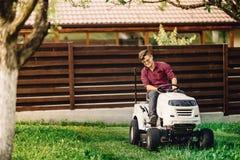 trabalhador que jardina e que faz ajardinando trabalhos, usando ferramentas e a maquinaria profissionais Fotografia de Stock