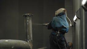 Trabalhador que limpa com jato de areia a tubulação de gás video estoque
